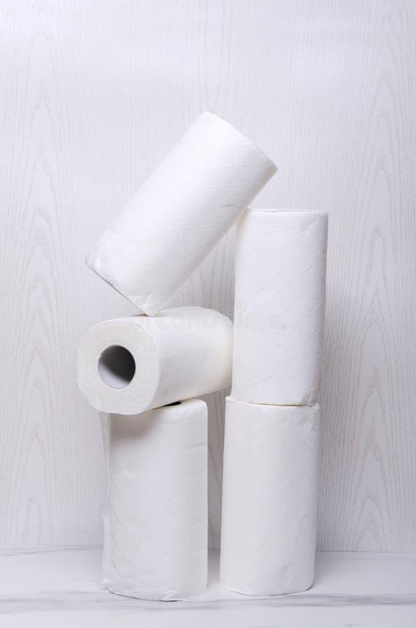 Tiro vertical de toallas de papel rodadas en el piso de mármol contra la pared blanca imagen de archivo