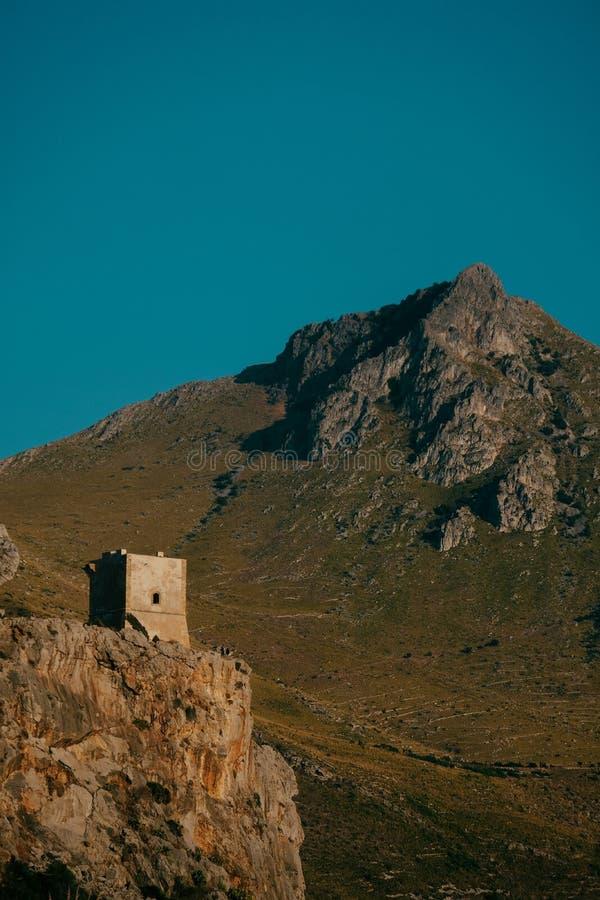 Tiro vertical de uma casa sobre o penhasco com uma montanha e um céu azul no fundo imagem de stock royalty free