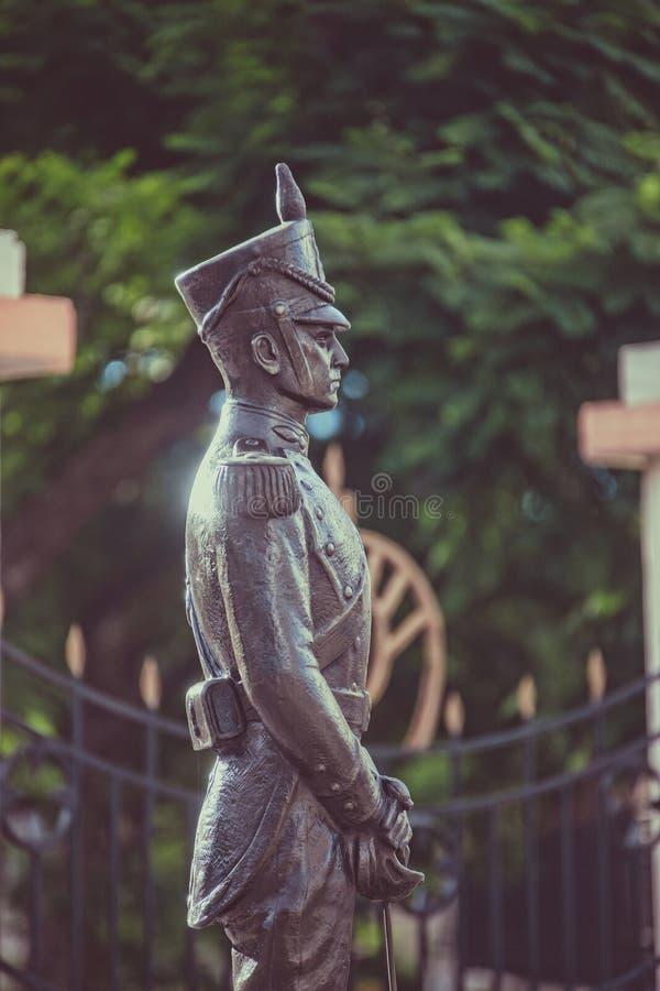 Tiro vertical de uma estátua de um soldado em um parque com um fundo borrado imagem de stock royalty free
