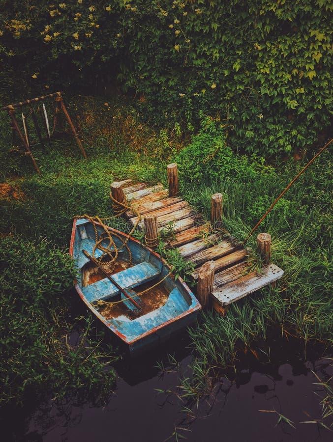 Tiro vertical de un barco viejo en el agua cerca de un muelle de madera rodeado por el verdor fotos de archivo