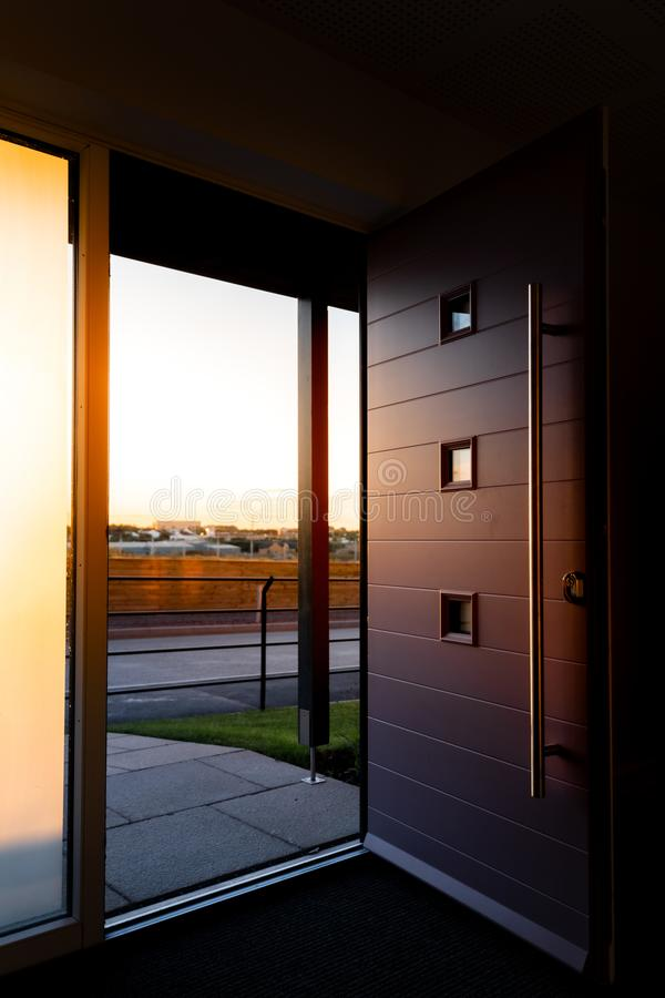 Tiro vertical de un foor delantero moderno abierto de par en par que muestra campos y de una puesta del sol en la distancia foto de archivo