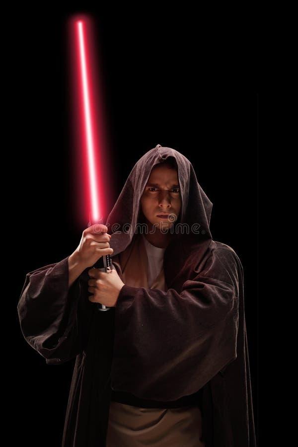 Tiro vertical de un guerrero con la espada del laser fotos de archivo
