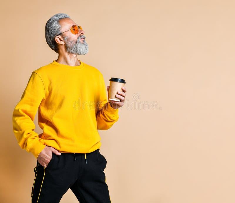 Tiro vertical de un mayor alegre que sostiene una taza del caf? con leche y que mira la c?mara imagen de archivo