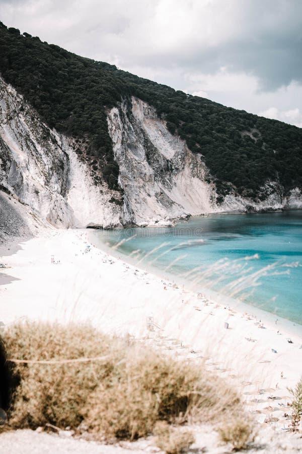 Tiro vertical de una costa hermosa del lago al lado de las montañas fotografía de archivo