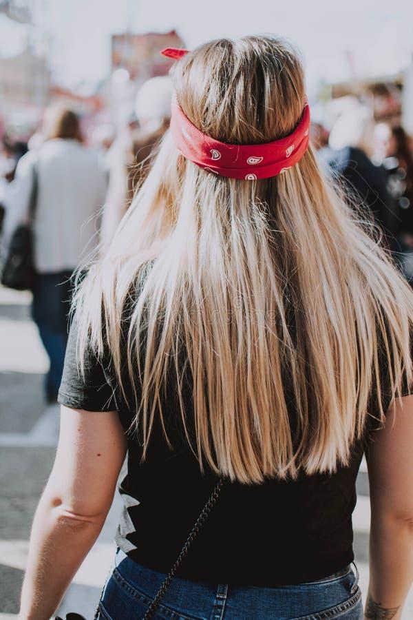 Tiro vertical de una hembra que lleva una venda roja que camina en una calle en un día soleado fotos de archivo libres de regalías