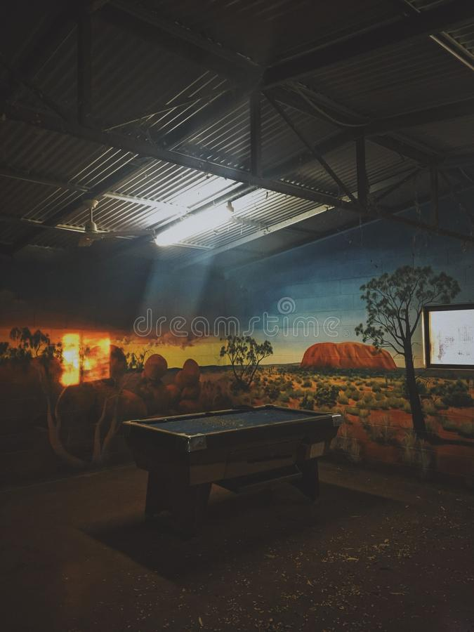 Tiro vertical de una mesa de billar en un cuarto con el dibujo en las paredes y encender brillante sobre él foto de archivo