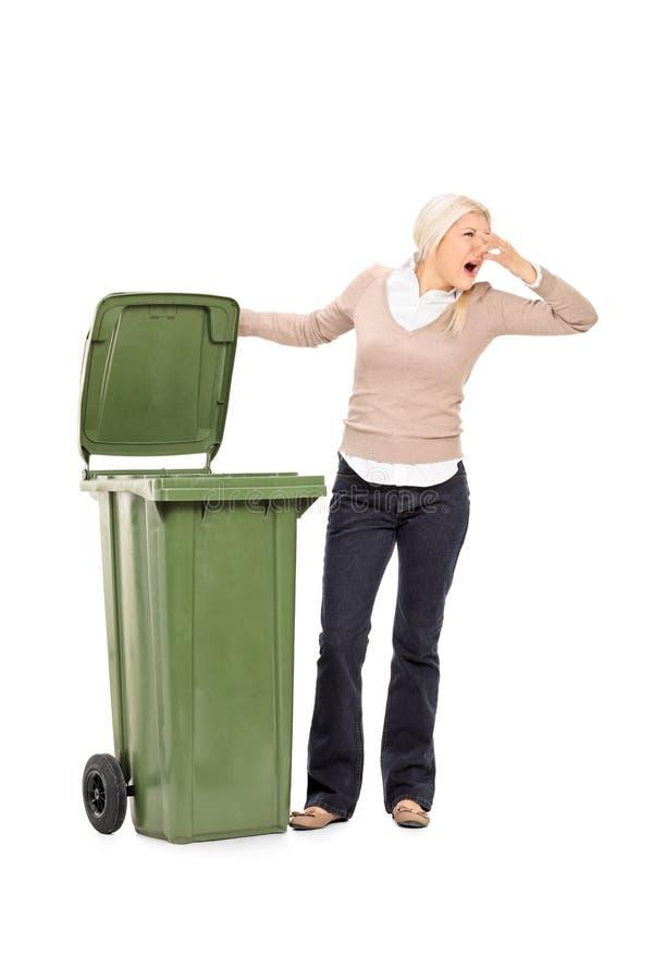 Tiro vertical de una mujer que abre un bote de basura stinky imágenes de archivo libres de regalías