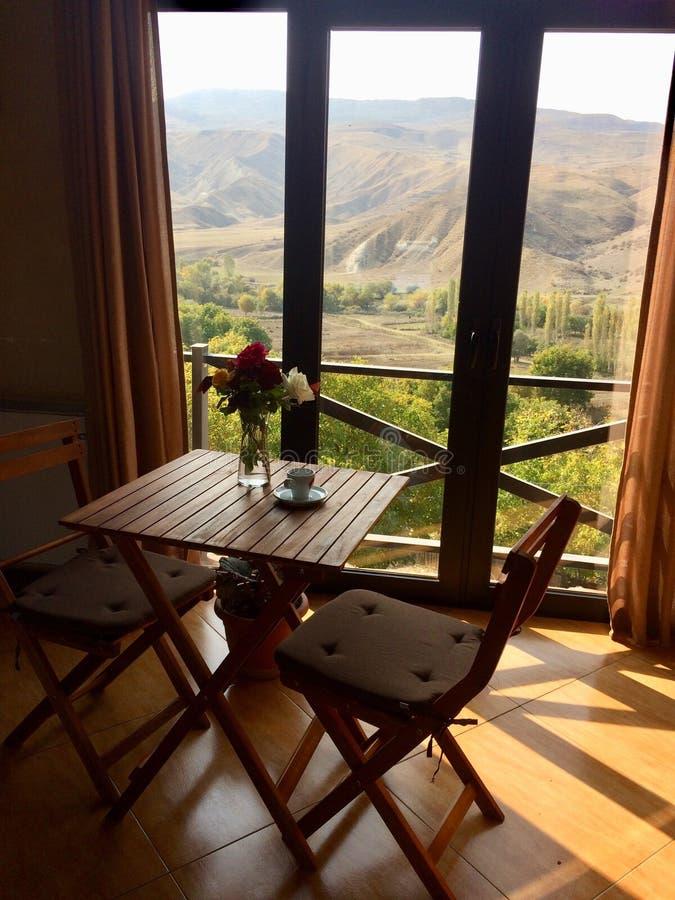 Tiro vertical de una pequeña mesa de comedor de madera con las sillas cerca de un balcón con una hermosa vista imagen de archivo libre de regalías
