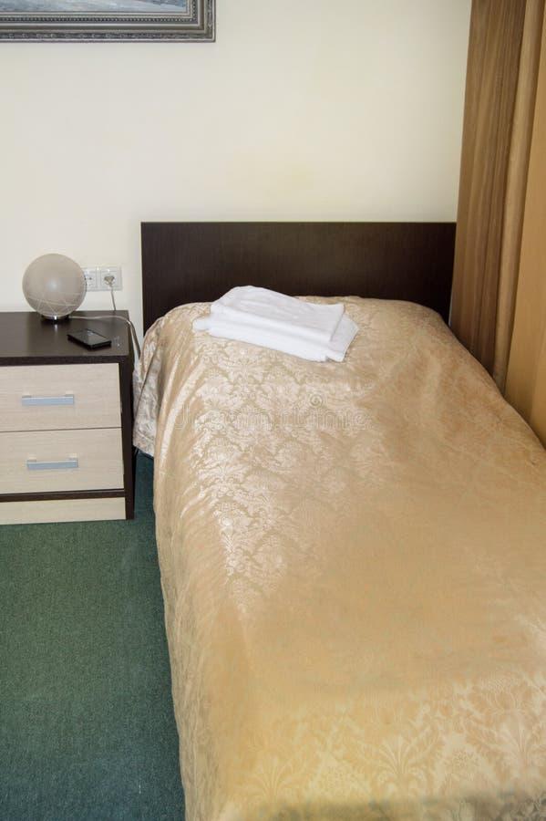 Tiro vertical del interior del dormitorio del hotel con una sola cama vacía con el cabecero y mesita de noche y toallas de madera fotos de archivo libres de regalías