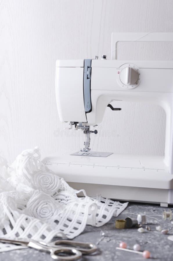 Tiro vertical del lugar de trabajo del sastre Máquina de coser, tela blanca, tijeras y diversos accesorios para la ropa de costur foto de archivo