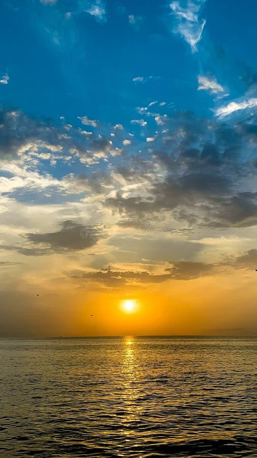 Tiro vertical del mar hermoso con el sol que brilla cerca del horizonte con las nubes impresionantes fotos de archivo libres de regalías