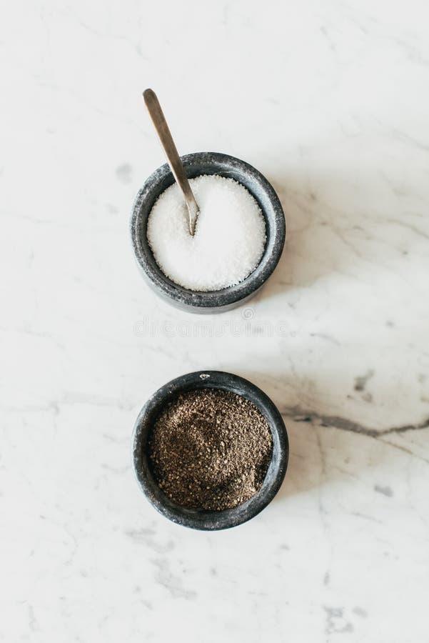 Tiro vertical del primer de la sal y de la pimienta en una tabla blanca texturizada imagenes de archivo