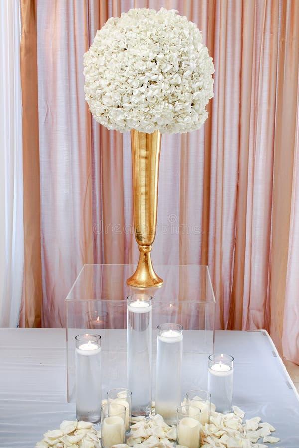 Tiro vertical del primer de una pieza central de la flor blanca en la caja de cristal clara con las velas fotografía de archivo