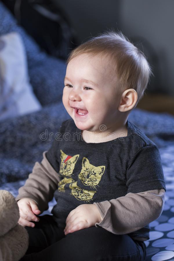 Tiro vertical do bebê justo bonito que senta-se na cama com vestir a camisa engraçada do gato fotografia de stock