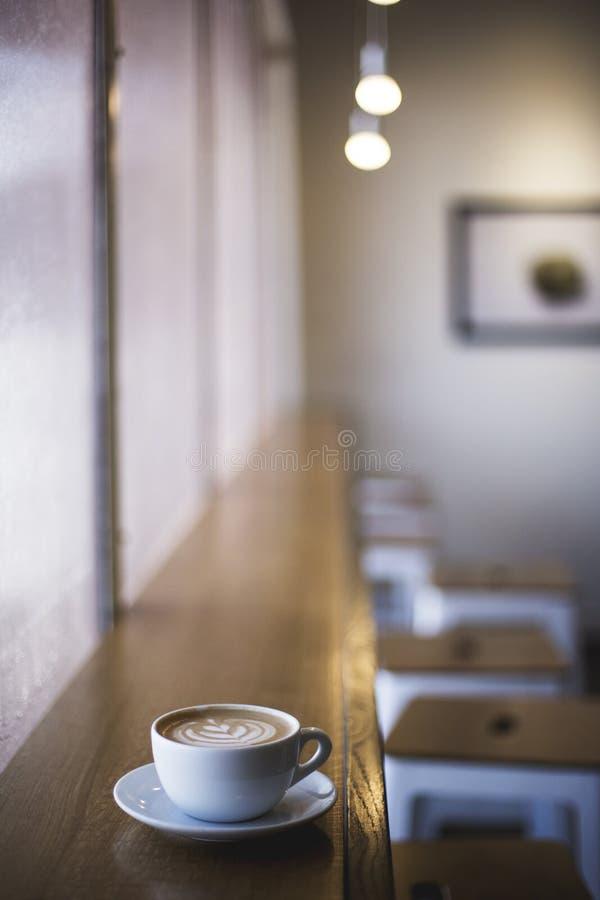 Tiro vertical do close up do copo branco do café da arte do latte em uma prateleira da janela em um café fotos de stock royalty free