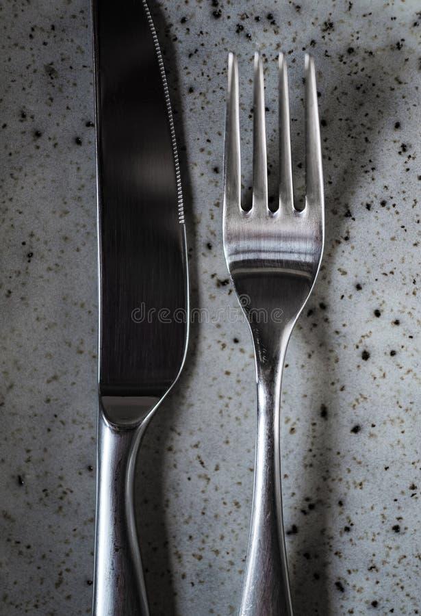 Tiro vertical do close up de uma faca de tabela de prata e de uma forquilha da tabela fotografia de stock royalty free