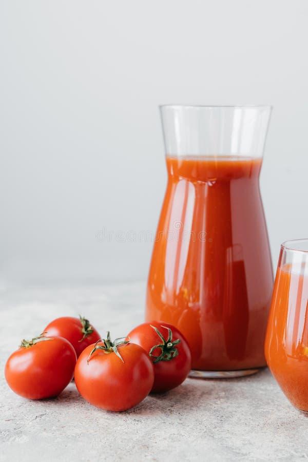 Tiro vertical isolado do suco de tomate recentemente feito, tomates maduros com as folhas verdes no fundo branco Vegetais complet fotos de stock royalty free