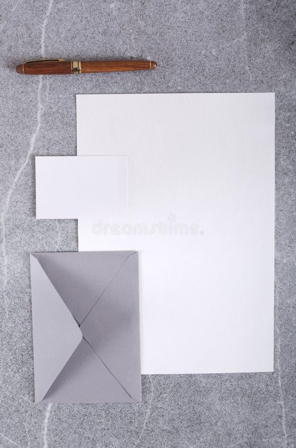 Tiro vertical Vista superior de la tarjeta de visita vacía, del sobre, de la pluma y de la hoja de papel en blanco en la tabla gr imagen de archivo libre de regalías