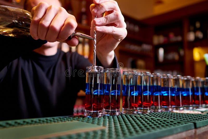 Tiros alcohólicos en contador de la barra El camarero profesional vierte tiros alcohólicos fotografía de archivo libre de regalías
