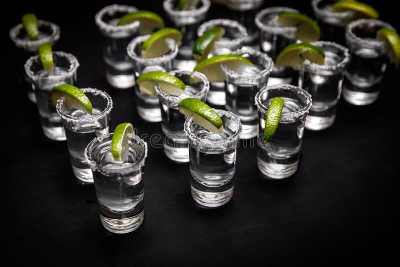 Tiros del Tequila con la cal y la sal en la tabla negra fotografía de archivo libre de regalías