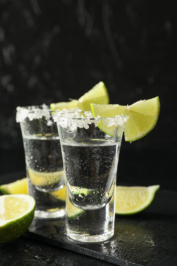 Tiros del Tequila con las rebanadas de la sal y de la cal en fondo negro imagen de archivo libre de regalías