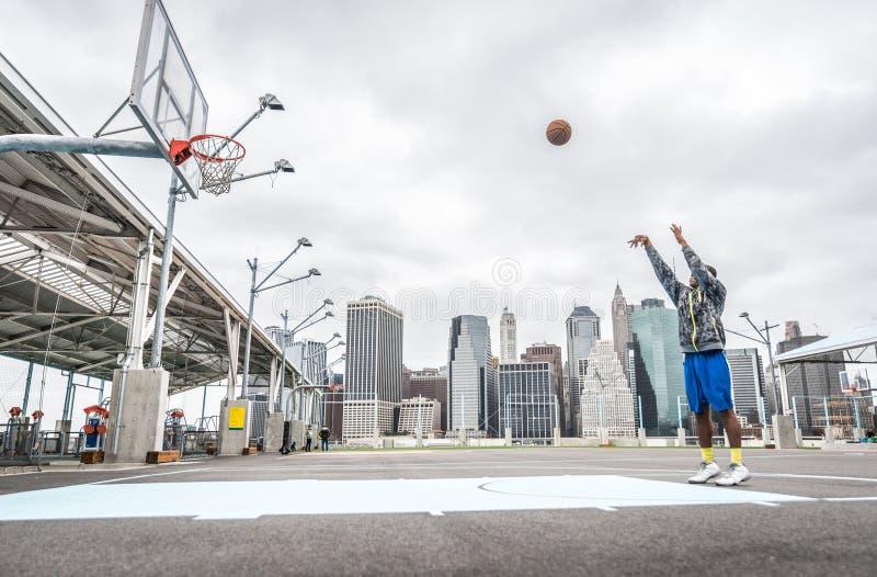 Tiros do treinamento do jogador de basquetebol na corte fotografia de stock