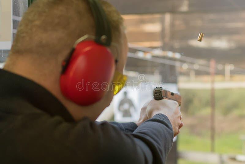 Tiroteo con una pistola Pistola de la leña del hombre en radio de tiro imagen de archivo libre de regalías