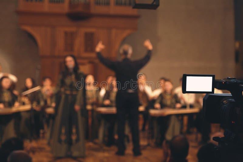 Tiroteo de la cámara de vídeo en el conductor de orquesta que dirige sinfonía imagenes de archivo