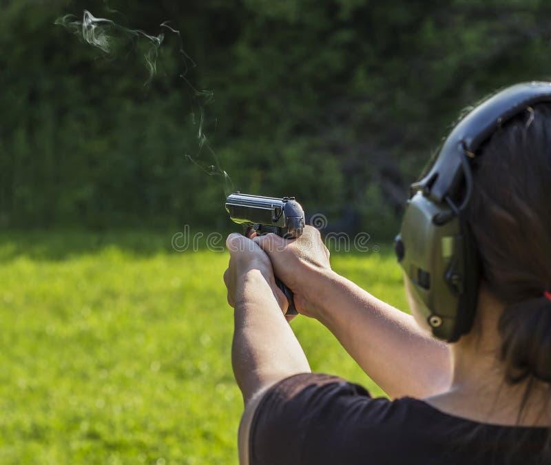 Tiroteo de la muchacha con un arma imagen de archivo libre de regalías