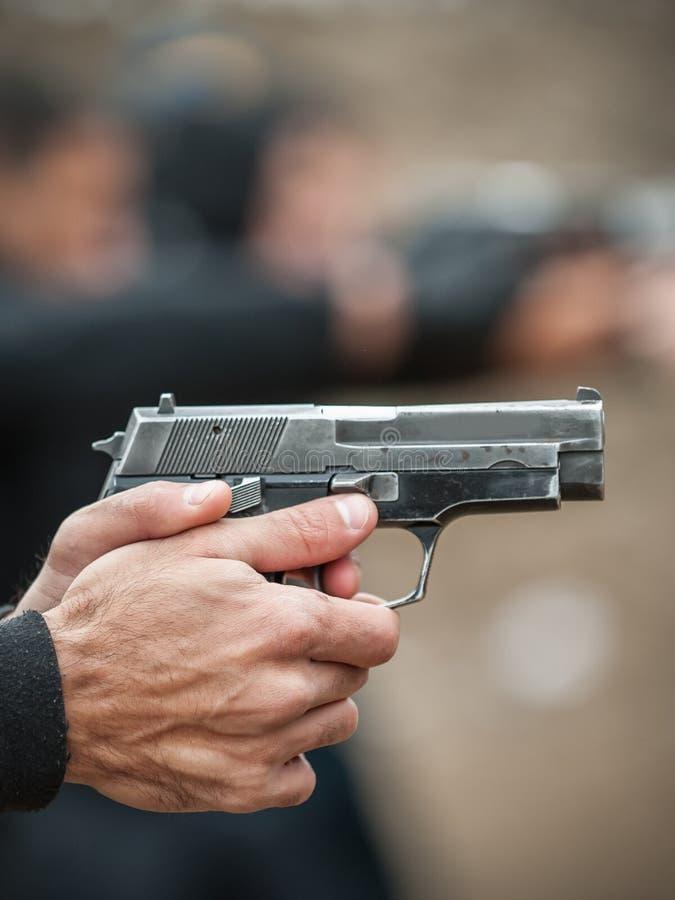 Tiroteo de la pistola de la mano izquierda y arma el sostenerse Opinión del detalle del primer imagen de archivo libre de regalías