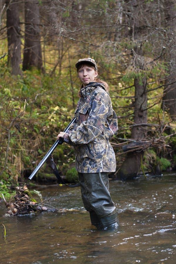 Tiroteo del cazador de la mujer en el pequeño río en el bosque fotos de archivo