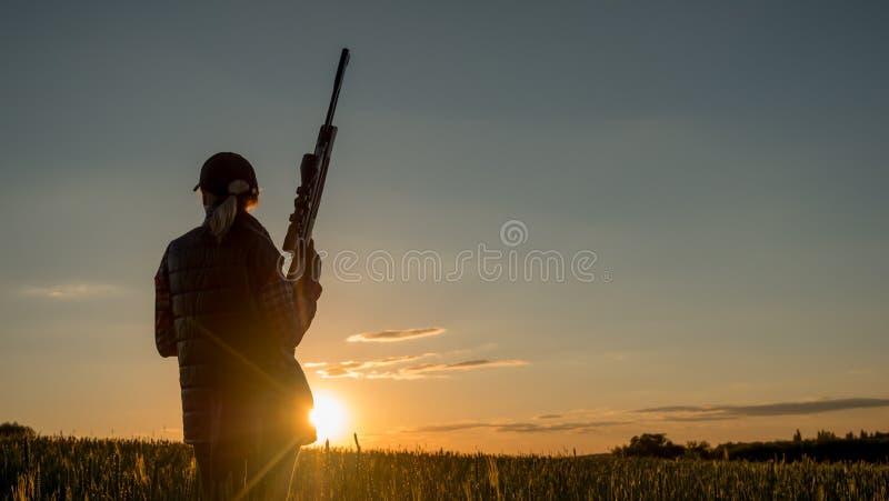 Tiroteo y caza - mujer del deporte con un rifle en la puesta del sol foto de archivo libre de regalías