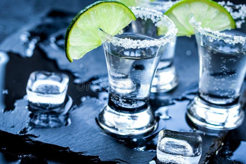 Tirs argentés de tequila avec de la glace et la chaux sur le fond noir de table photographie stock