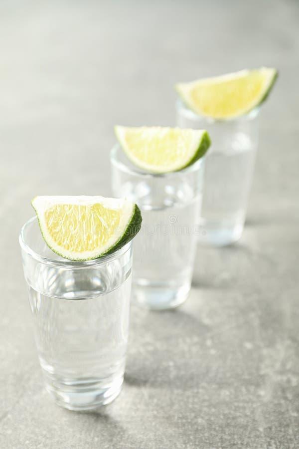 Tirs de tequila avec des tranches de chaux photographie stock