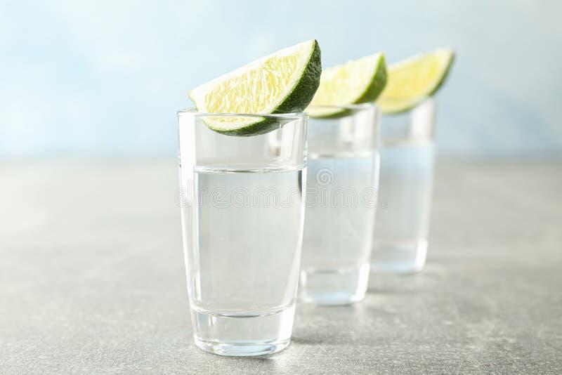 Tirs de tequila avec des tranches de chaux photographie stock libre de droits