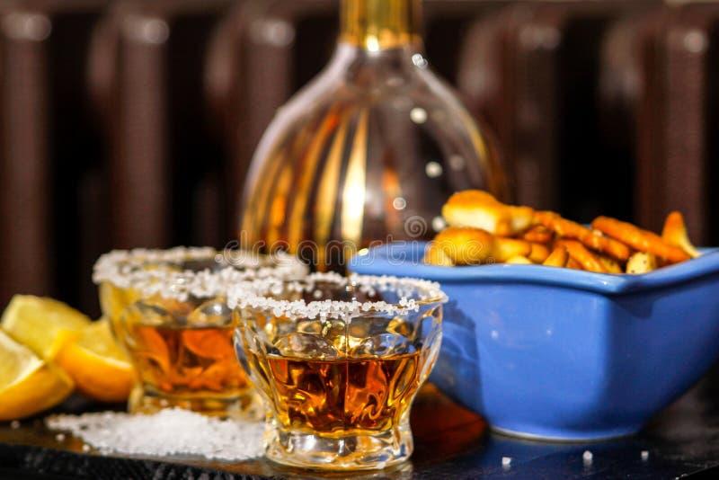 Tirs de tequila avec du sel, le citron et les casse-croûte photos stock