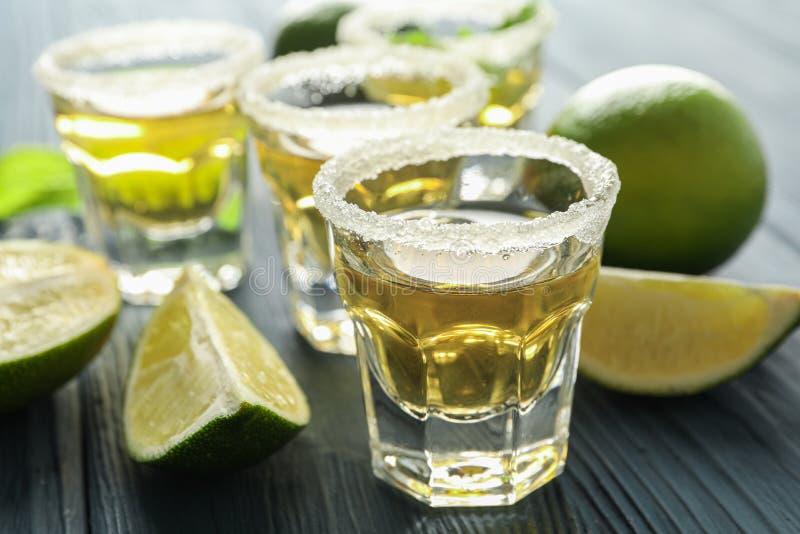 Tirs de tequila, sel, tranches de chaux et menthe sur la table en bois images stock