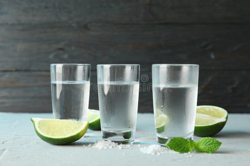 Tirs de tequila, sel, tranches de chaux et menthe sur la table image libre de droits