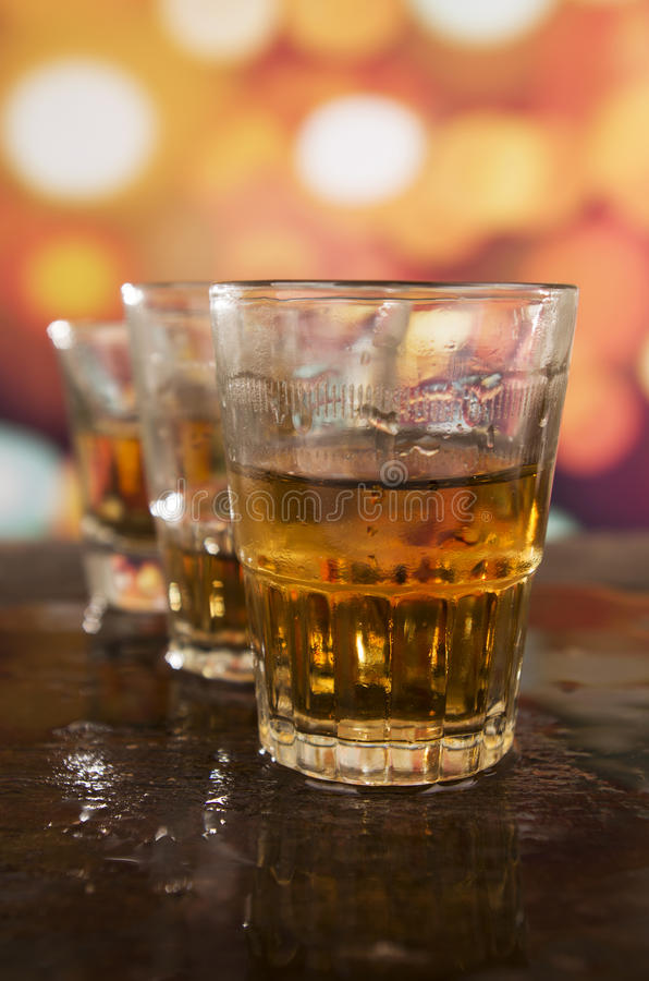 Tirs de whiskey de rhum au-dessus des lumières defocused photos stock