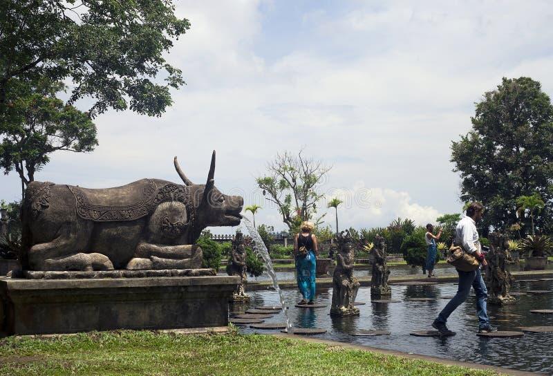 Tirta Gangga tidigare kunglig vattenslott och gåturister royaltyfria bilder