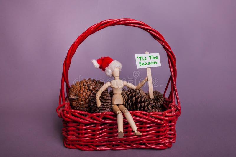 Tis sezonu palika znak trzymający spajającą manikin lalą jest ubranym Santa sosny i kosza rożków bożych narodzeń kapeluszową czer zdjęcia stock