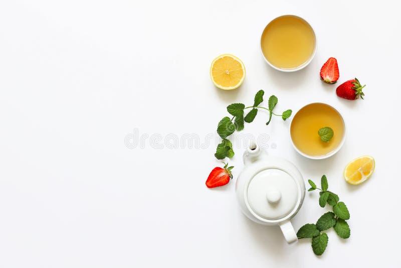 Tisana dalla menta e dalla fragola con il limone altre erbe su un fondo bianco T immagini stock