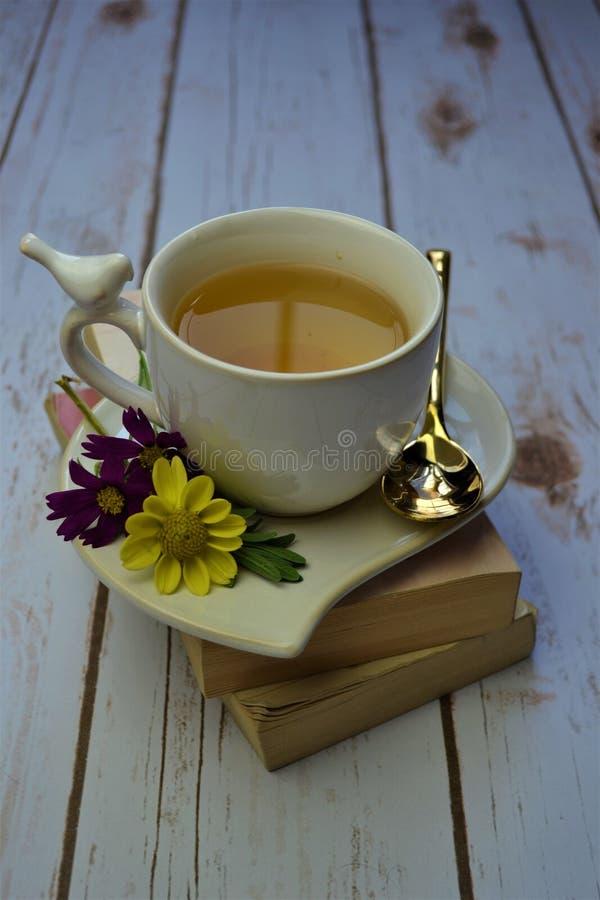 Tisana sulla pila di libri con i fiori fotografie stock