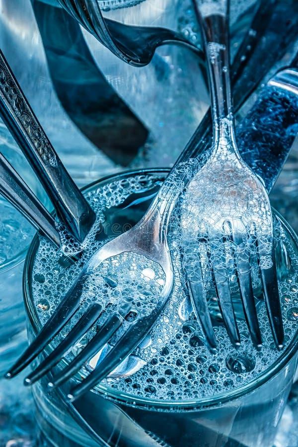 Tischbesteck, das mit Wasser und Reinigungsmittel gewaschen wird stockfotos