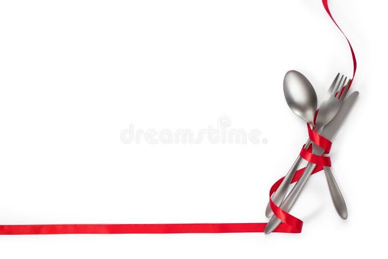 Tischbesteck mit rotem Band als Grenze auf weißem Hintergrund w stockbild