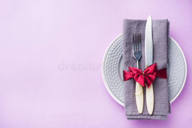 Tischbesteck, Plattenmesser und Gabel mit Serviette auf rosa Hintergrund Feiertagstabellenkonzept stockfoto