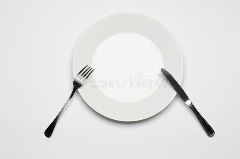 Tischbesteck- und Restaurantthema: Gabelmesser und weiße Platte, die auf einer weißen Tabelle lokalisiert in der Draufsicht des S lizenzfreie stockfotografie