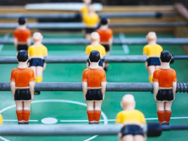 Tischfußball-Fußballspiel mit den roten und gelben Spielern Team lizenzfreie stockfotos
