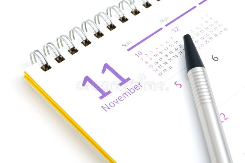 Tischkalender und Stift auf weißem Hintergrund lizenzfreies stockfoto