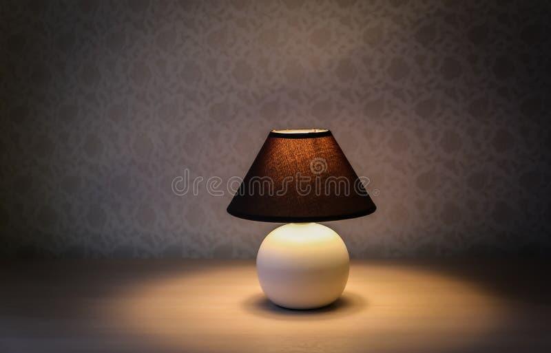 Tischlampe mit braunem Schatten auf einem Holztisch stockbild